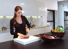 Kvinna i bitande grönsak för kök Royaltyfri Bild