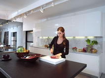 Kvinna i bitande ingredienser för kök Royaltyfria Bilder