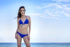 Kvinna i blå bikini, på stranden Se kameran arkivfoto