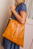 Kvinna i blåttklänningen som rymmer ett ljus - brun handväska royaltyfria bilder