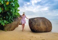 Kvinna i blommaklänning på stranden arkivbild