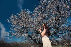 Kvinna i blommande träd Arkivfoto