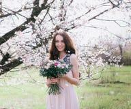 Kvinna i blommande träd Kvinna med bröllopbuketten i händer Royaltyfri Fotografi