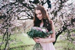 Kvinna i blommande träd Kvinna med bröllopbuketten i händer Royaltyfria Bilder