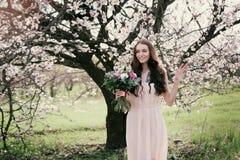 Kvinna i blommande träd Kvinna med bröllopbuketten i händer Royaltyfri Foto