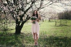 Kvinna i blommande träd Kvinna med bröllopbuketten i händer Royaltyfria Foton