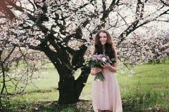 Kvinna i blommande träd Kvinna med bröllopbuketten i händer Fotografering för Bildbyråer
