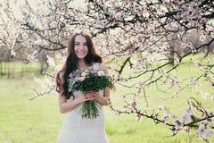 Kvinna i blommande träd Kvinna med bröllopbuketten i händer Royaltyfri Bild