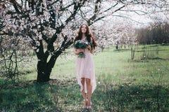 Kvinna i blommande träd Kvinna med bröllopbuketten i händer Arkivfoton