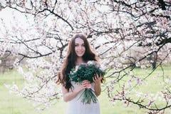 Kvinna i blommande träd Kvinna med bröllopbuketten i händer Arkivbild