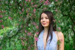 Kvinna i blomningfilialerna av ett träd Arkivfoton