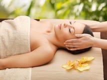 Kvinna i brunnsorten som får ansikts- massage arkivbild