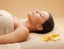 Kvinna i brunnsortsalongen som ligger på massageskrivbordet Royaltyfri Fotografi