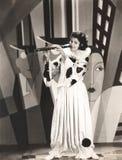 Kvinna i clowndräkten som spelar klarinetten arkivbild