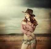 Kvinna i cowboyhatt och sexiga kortslutningar Arkivbilder