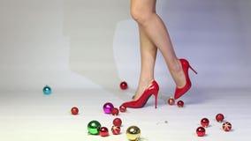Kvinna i de röda höga hälen som spelar med julbollar stock video