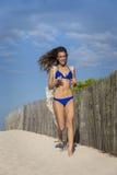 Kvinna i den blåa bikinin som kör på stranden Se kameran royaltyfri fotografi
