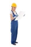Kvinna i den blåa byggmästarelikformign med byggnadsplan som isoleras på whi Arkivbild