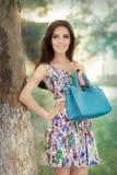 Kvinna i den blom- klänningen som rymmer den stilfulla handväskan Arkivbilder