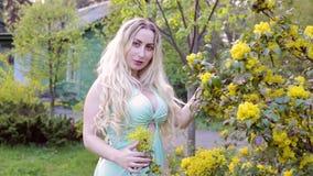 Kvinna i den blommiga tr?dg?rden stock video