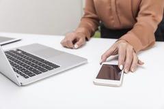 Kvinna i den bruna blusen som når för hennes mobiltelefon Arkivbild