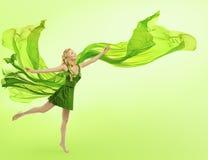Kvinna i den gröna klänningen som blåser torkduken, siden- tyg för ung flicka Arkivfoto