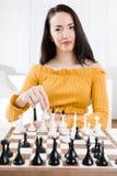 Kvinna i den gula klänningen som framme sitter av schack - din flyttning arkivbilder