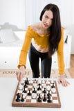 Kvinna i den gula klänningen som framme sitter av schack - flyttning för vit häst arkivfoto