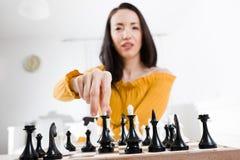 Kvinna i den gula klänningen som framme sitter av schack - gå att segra royaltyfria bilder