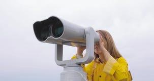 Kvinna i den gula regnrocken som ser till och med turist- kikare på bergen lager videofilmer