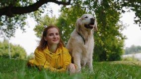 Kvinna i den gula regnrocken som sitter med en hund stock video