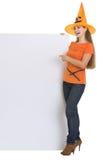 Kvinna i den Halloween hatten som pekar på blank affischtavla Royaltyfri Foto