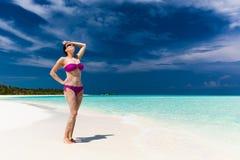 Kvinna i den purpurfärgade bikinin som täckas i sand på den tropiska stranden arkivbild