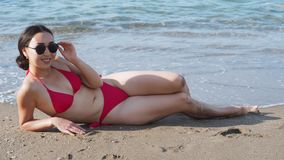 Kvinna i den röda baddräkten som ligger på stranden och solbada arkivfilmer