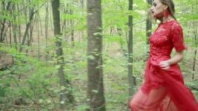 Kvinna i den röda klänningen som är rinnande bort i skog
