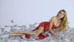 Kvinna i den röda klänningen som ligger på pengar sedel äganderätt för home tangent för affärsidé som guld- ner skyen till lätta  lager videofilmer