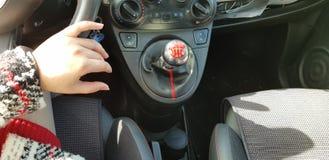 Kvinna i den röda mini- klänningen som sitter på chaufförplats hennes hand på styrninghjulet arkivbild