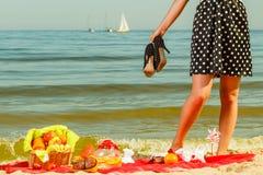Kvinna i den retro klänningen som har picknicken nära havet Fotografering för Bildbyråer