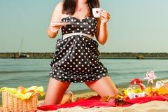 Kvinna i den retro klänningen som har picknicken nära havet Arkivfoto