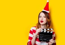 Kvinna i den Santa Claus hatten med filmmakingclapperboard Arkivbilder