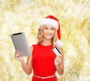 Kvinna i den santa hatten med den minnestavlaPC och kreditkorten Arkivbild