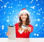 Kvinna i den santa hatten med den minnestavlaPC och kreditkorten Royaltyfri Foto