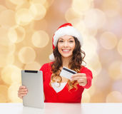 Kvinna i den santa hatten med den minnestavlaPC och kreditkorten Fotografering för Bildbyråer