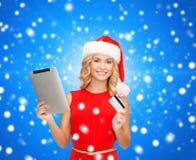 Kvinna i den santa hatten med den minnestavlaPC och kreditkorten Arkivbilder