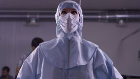 Kvinna i den skyddande dräkten som är rädd av virus Kvinnlig doktor i skyddande kläder kvinna i blå medicinsk skyddande dräkt arkivfilmer