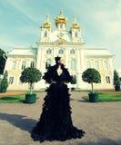 kvinna i den svarta klänningen som poserar bredvid slotten Fotografering för Bildbyråer