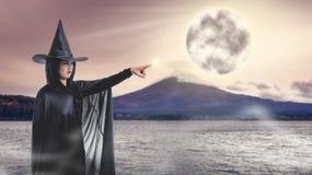 Kvinna i den svarta läskiga häxahalloween dräkten med Mount Fuji och royaltyfria foton