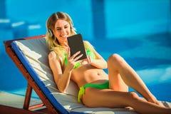 Kvinna i den tropiska solen nära simbassäng royaltyfri fotografi