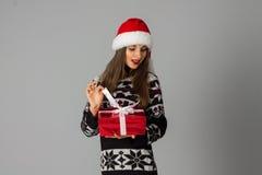 Kvinna i den varma tröja och santa hatten med den röda gåvan royaltyfri bild