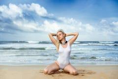 Kvinna i den vita baddräkten på stranden Royaltyfri Bild